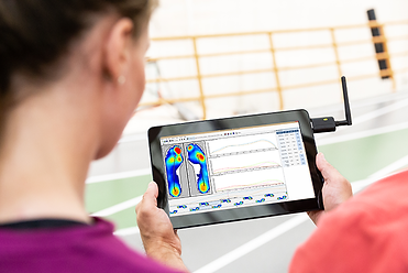 An athlete and trainer review foot & pressure statistics and gait measurements on a tablet with Pro Foot & Gait V8 software.