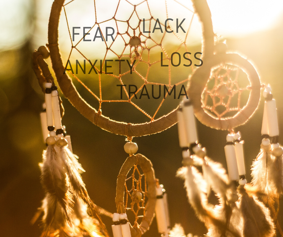 A dream catcher blowing in morning sun with the words fear, lack, loss, trauma, and anxiety written on it as they burn off in the morning light.