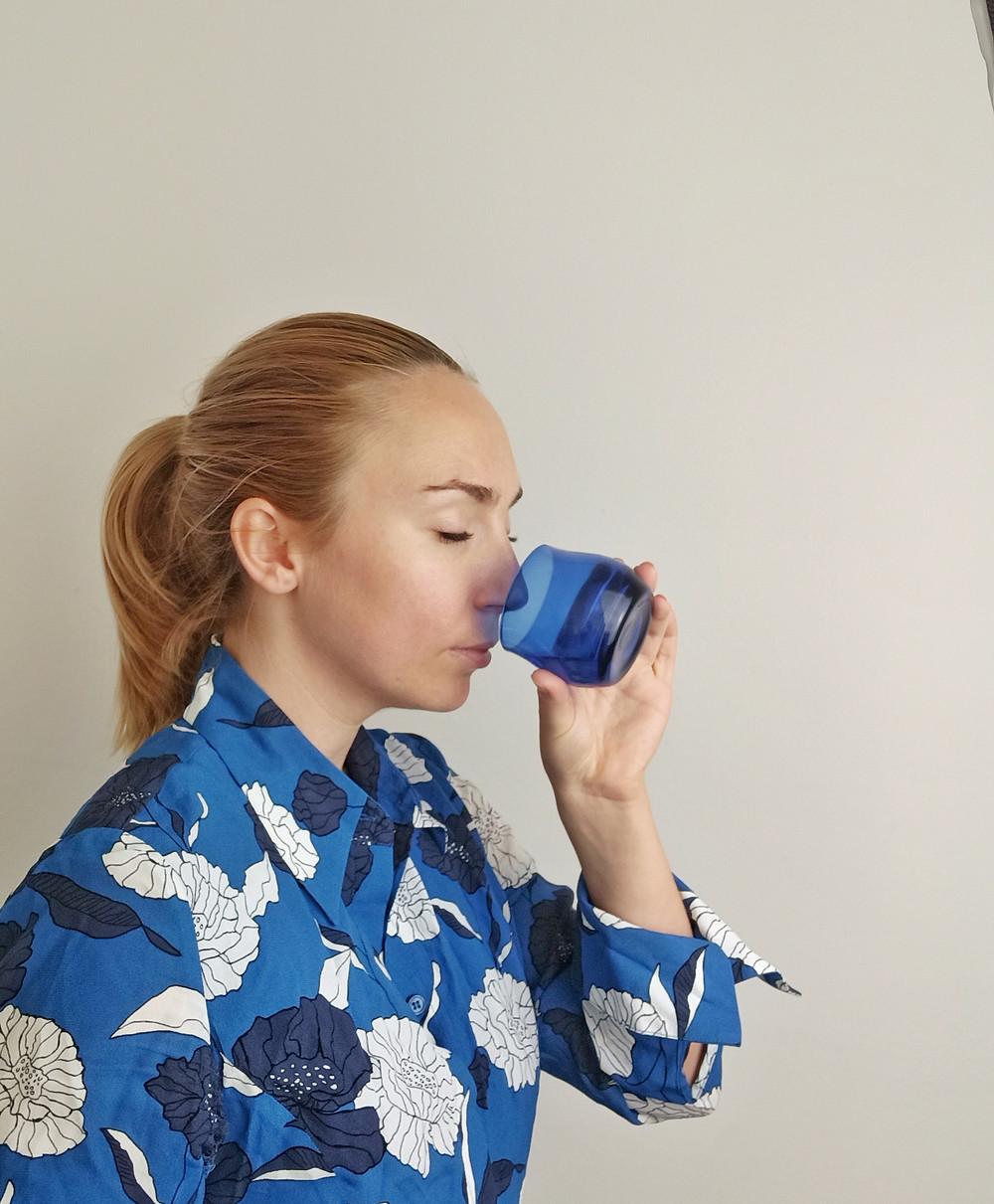 melanie pascal riecht an einem blauen originalen olivenöl glas für die verkostung