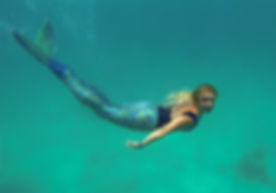 Mermaid in the sea, beautiful blond woman with fish mermaid tail swimming underwater in the blue gre