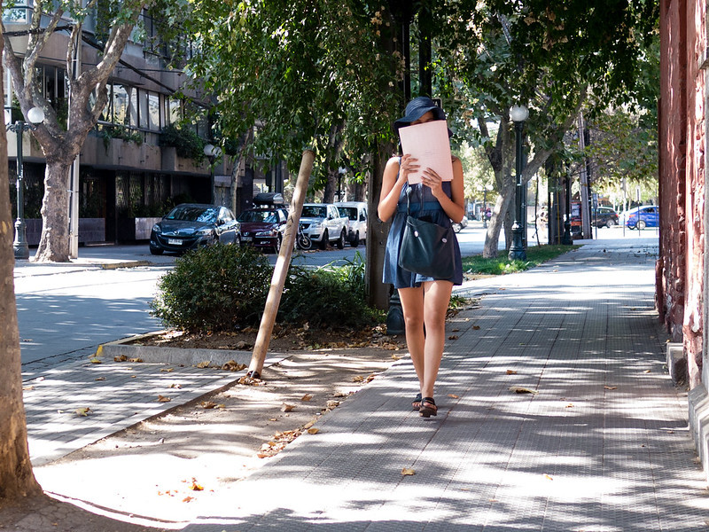 Frau geht lesend auf der Straße