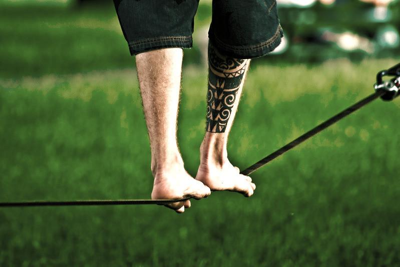 Mann mit Tattoo auf Unterschenkel auf Slackline.