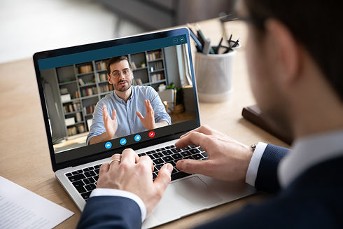 Back view of businessman talk with male business partner using video call on laptop discus