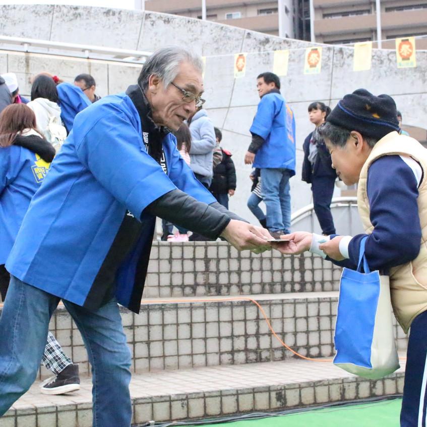 くじ引き抽選会で景品を手渡す西浜会長(左)