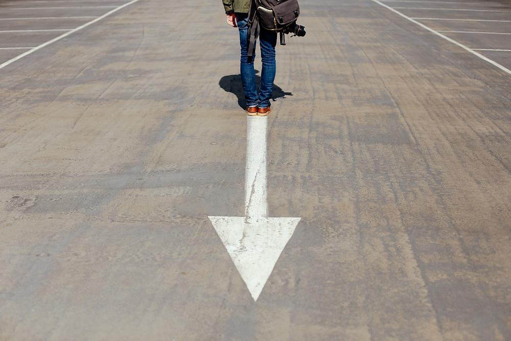 Man Standing on Arrow in Street