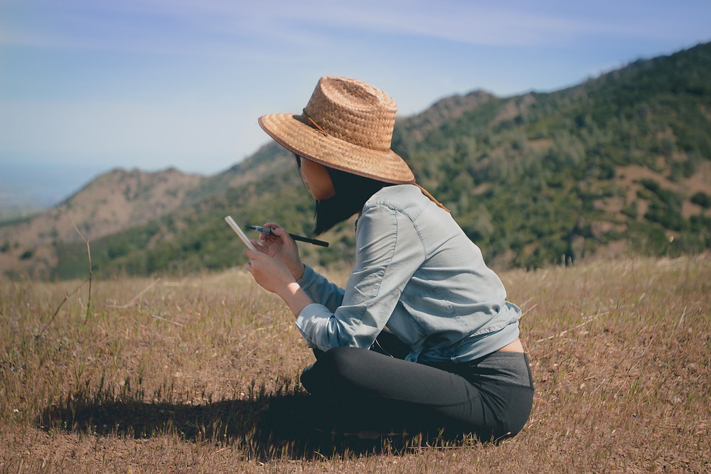 Woman Sitting Wearing Hat and Writing in Journal