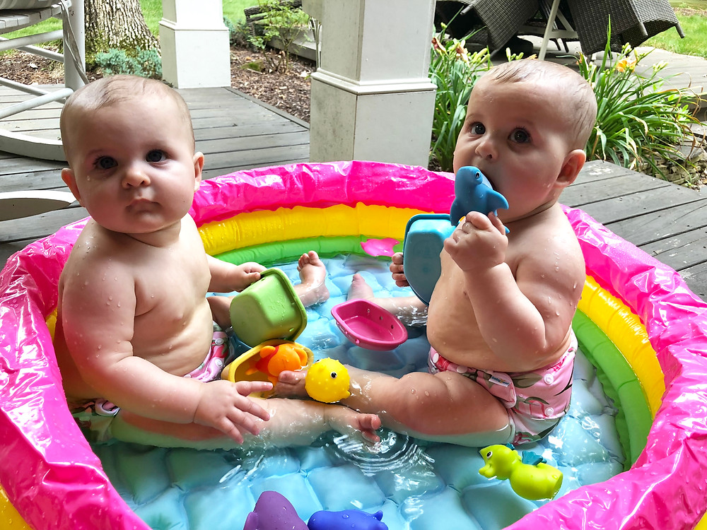twin girls in inflatable pool