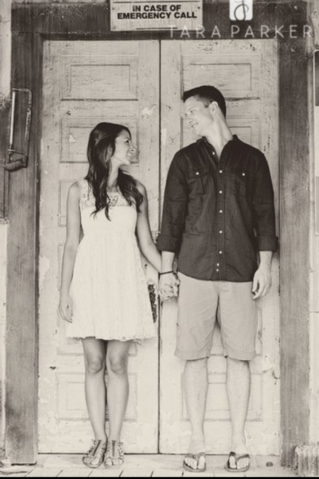 girl and boy looking at each other in doorway engagement photoshoot