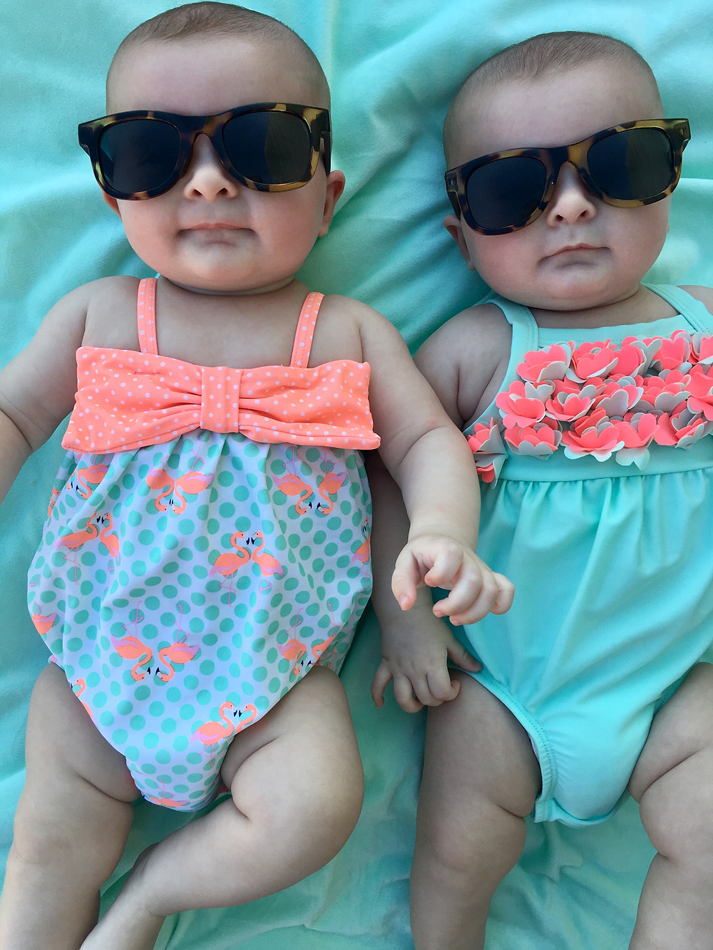 Twin girls in sunglasses and swimsuits