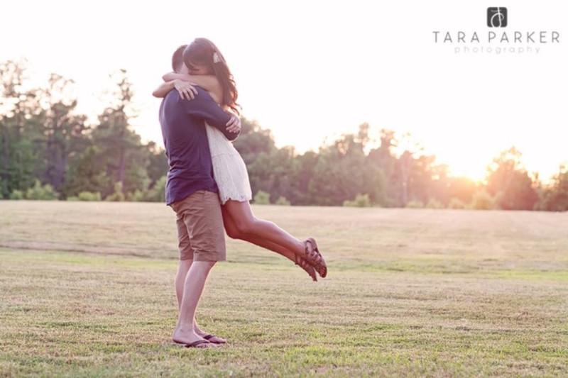 boy hugging girl in field engagement shot