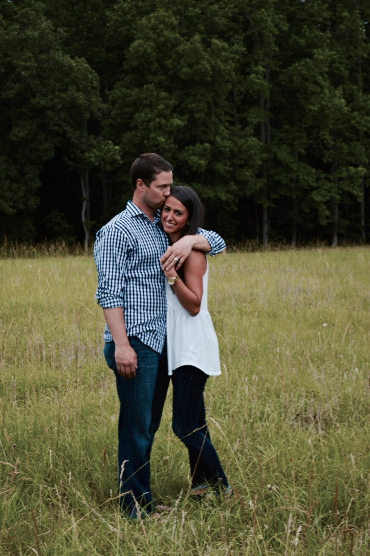 man kissing woman's forehead in field