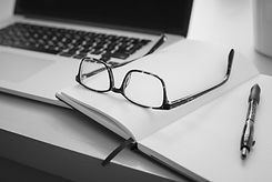 A desk and glasses are shown here to represent the online webinars that Lisa Crispo runs to help teach photographers at any level about photography