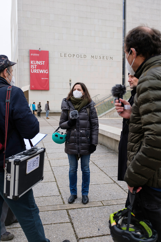 Frau mit Mikrofon vor Museum