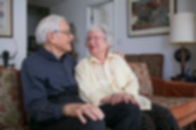 A white-haired couple smiling a each other