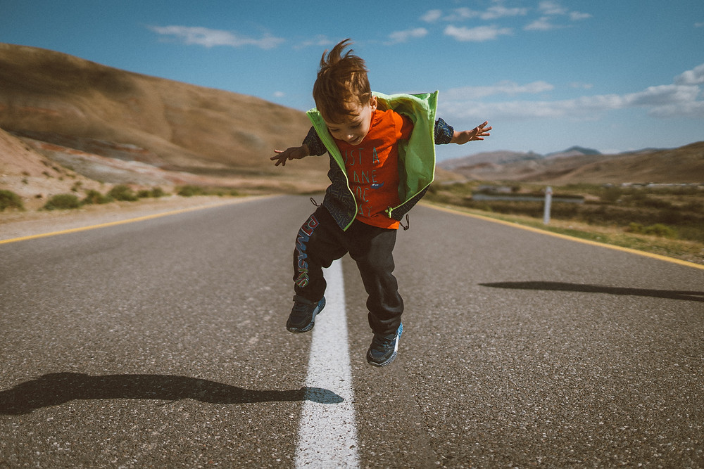 Kid jumping in the middle of the road