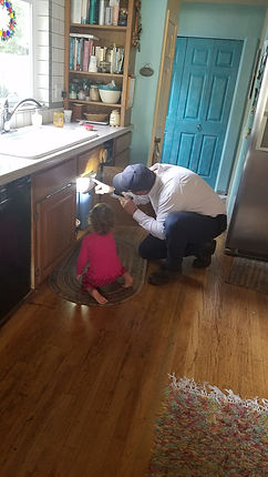 Service technician performing a pest inspection with a littl girl.  looking for cockroaches, ants, spiders, rats, bed bugs, thorough inspecton.