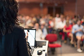 Rear view of business woman at lectern l
