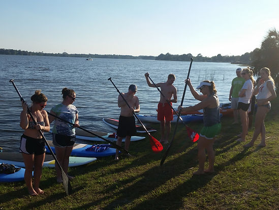 Instructor teaching Stand Up Paddle Board lessons to a group