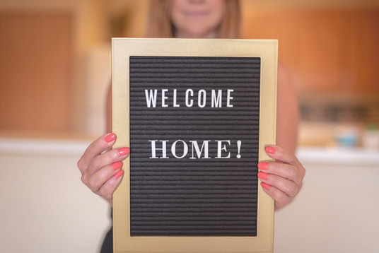 welcome-home-sign-being-held-up-by-happy