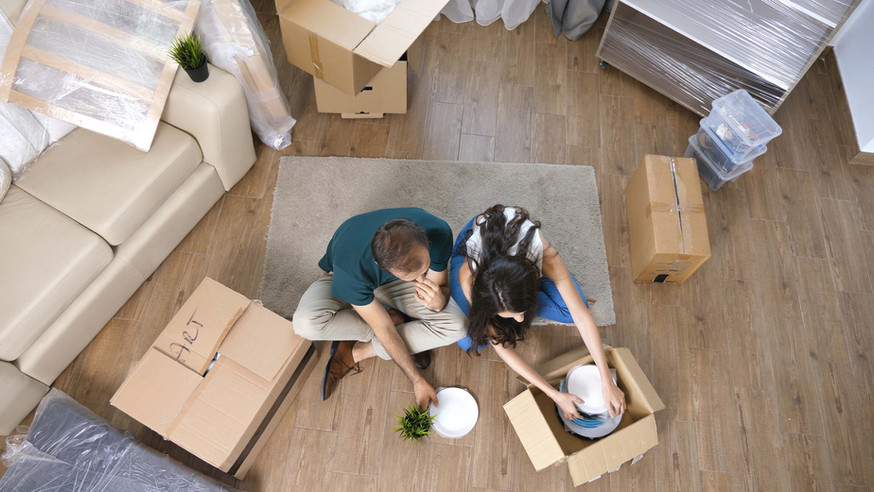 young-couple-moving-in-new-home-and-unpa