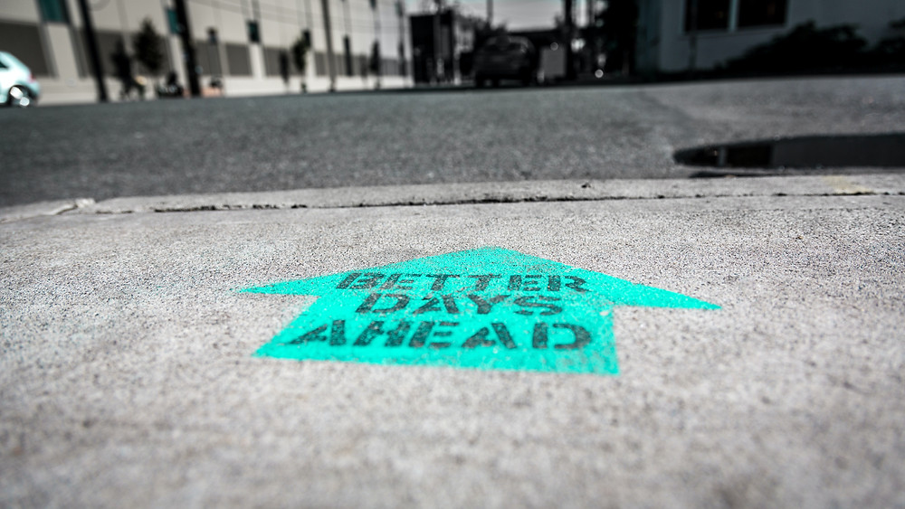 Painted arrow on the street emphasizing better days are ahead.