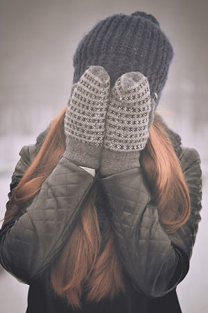 woman with mittens covering her face.