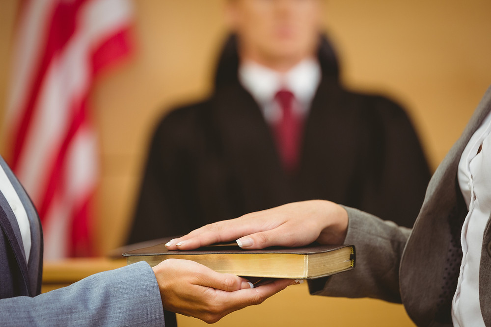 Woman's hand on a bible in front of a judge