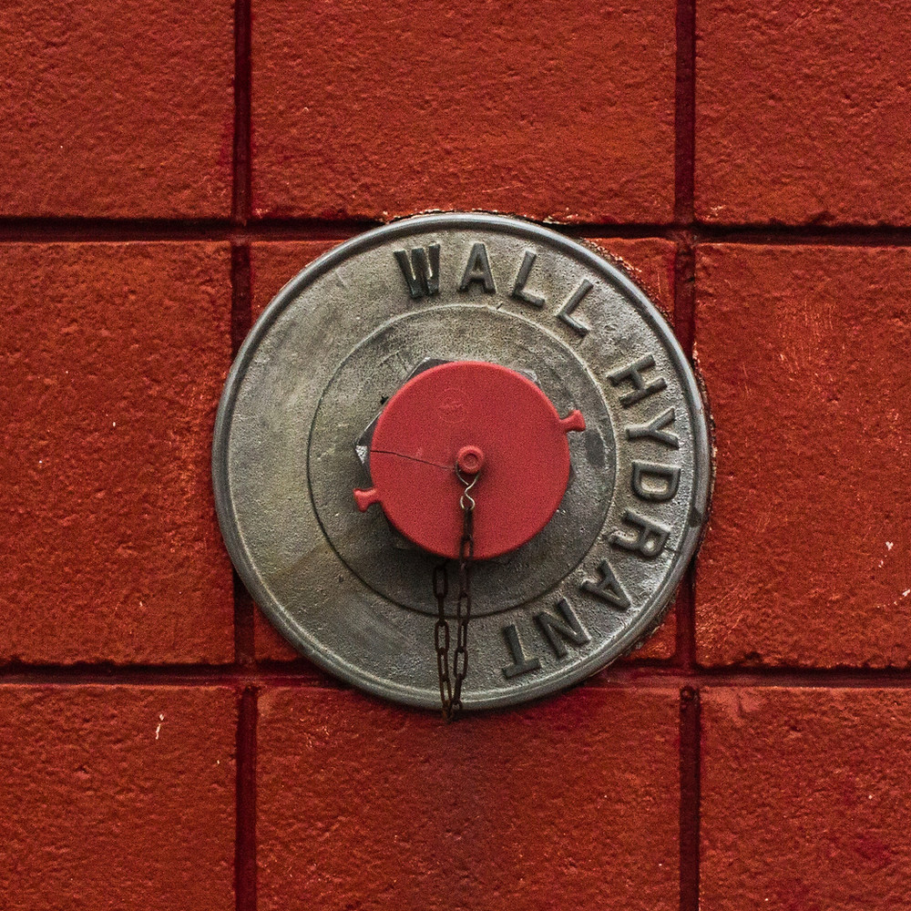 wall fire hydrant on red brick wall