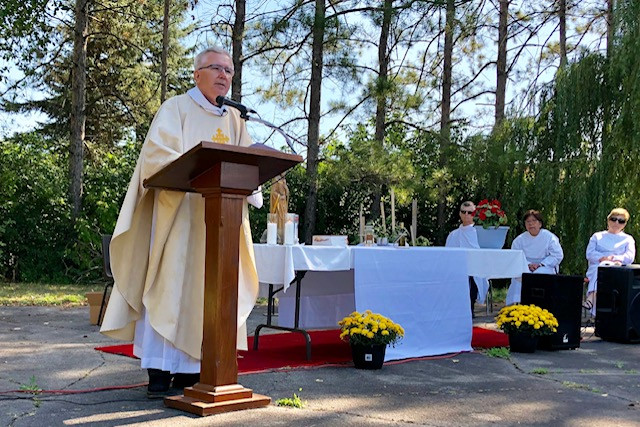 Fr. Frank delivers a homily in front of a beautiful evergreen background at the outdoor parish feast day mass, August 25, 2019.
