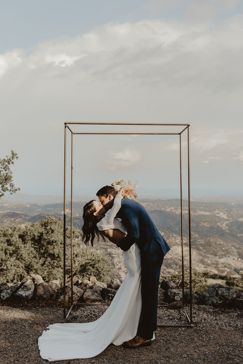 Bride and groom kissing in front of copper arch
