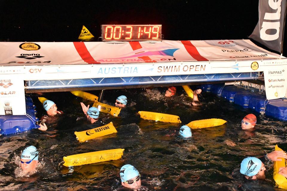 Die Teilnehmer des Vollmondschwimmen 2019 kommen durch den zielbogen