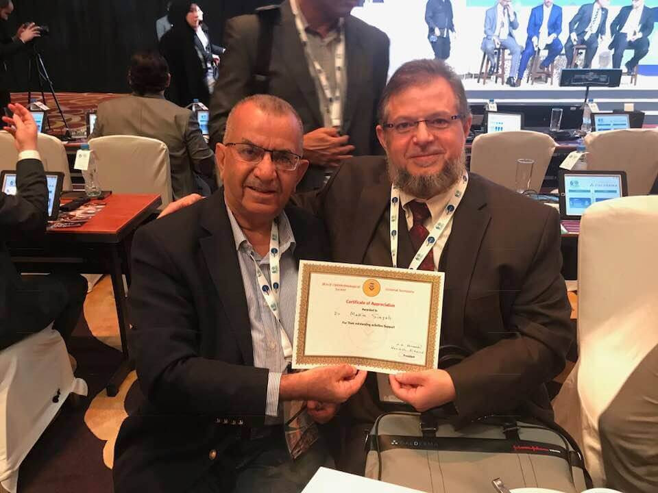 On the sidelines of the EPOMIC Conference, Dr. Mazen Sinjab receives the appreciation certificate from the head of the Iraqi delegation attending the conference. The appreciation certificate came for Dr. Mazen Sinjab efforts in medical education.