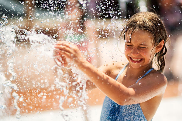 Young child playing in water splashes