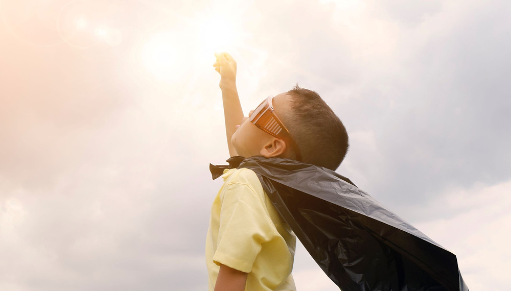 Child raising fist to the sky in success at overcoming test anxiety.