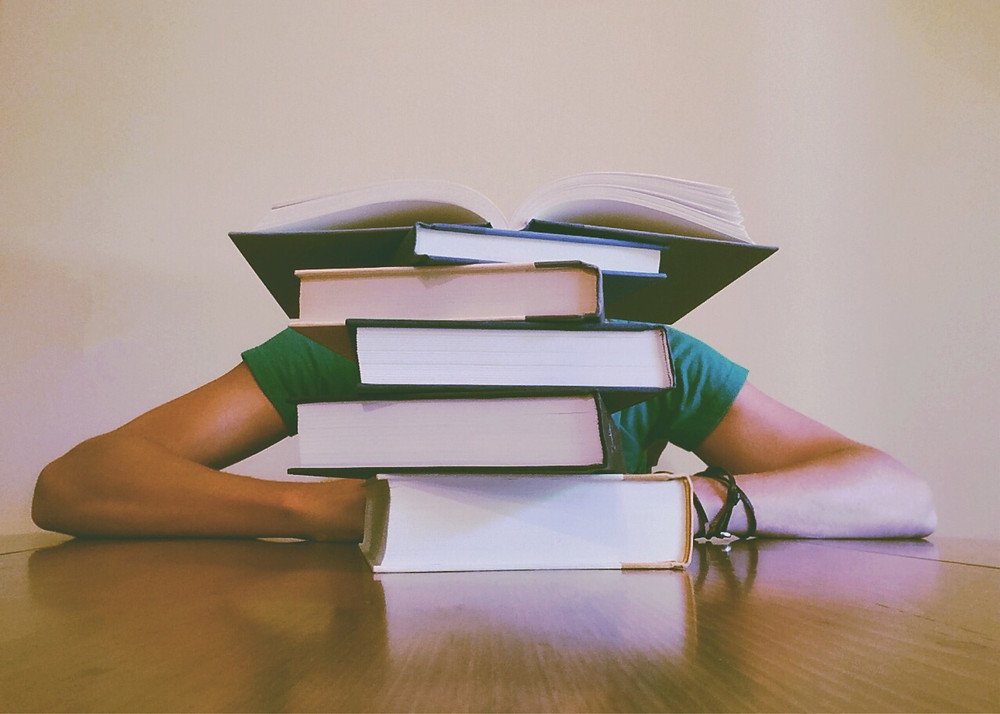 image of teen behind stack of books feeling overwhlemed