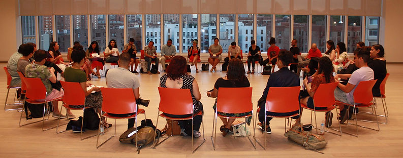 CantoMundistas at the retreat sit in a circle of red chairs