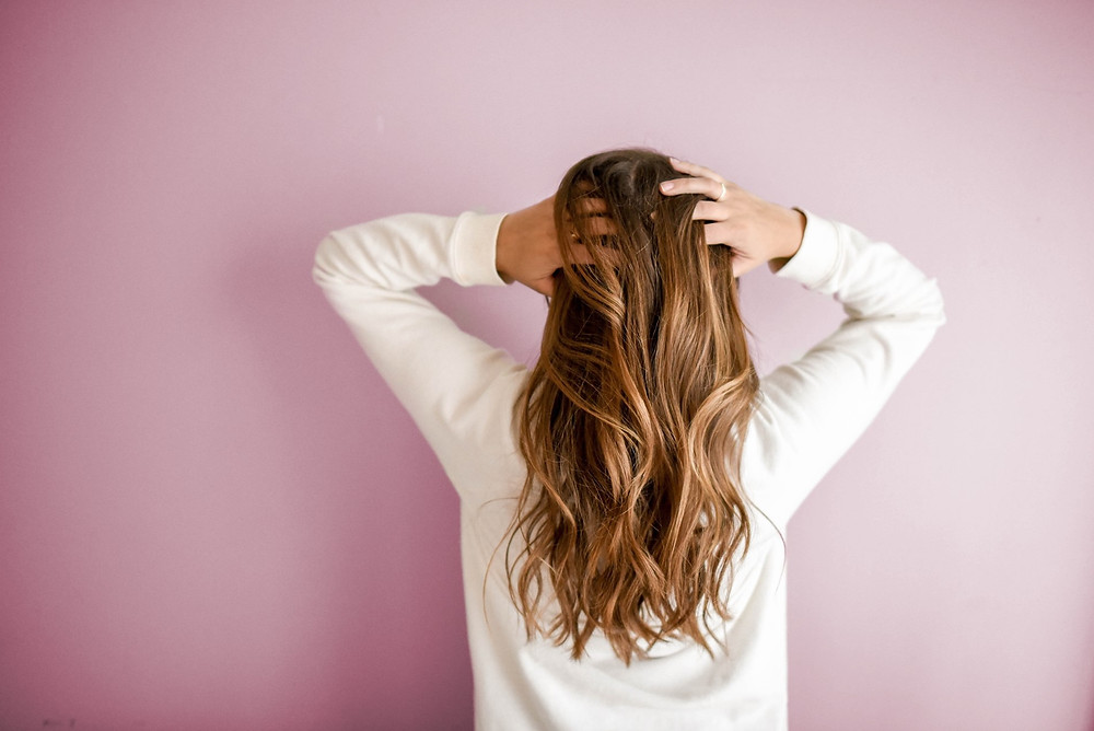 Woman with long hair extensions with the pink backdrop