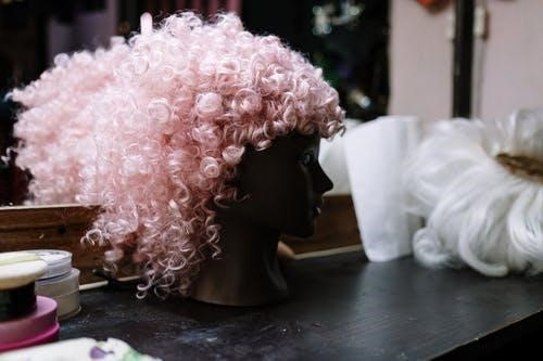 A pink curly wig on a mannequin head on a dressing table
