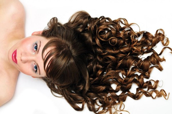 Girl with long curly hair lying down.