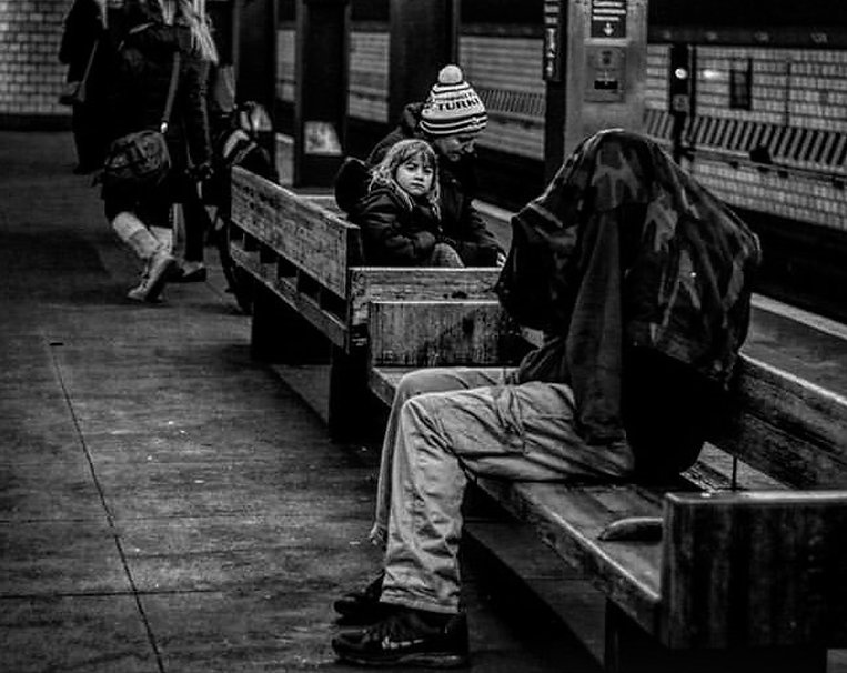 Child looks at homeless man hiding under a coat on NYC subway platform - Street photography