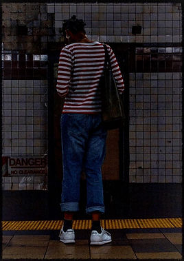 Woman in a striped shirt stands on a subway platform checking her phone - Street photography