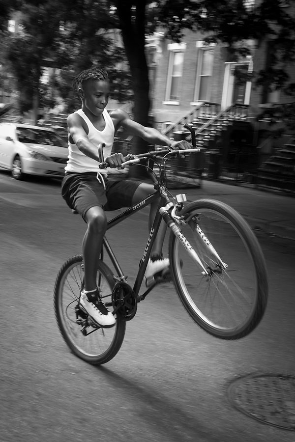 boy riding his bike - popping a wheely in Brooklyn, NY- Black and white photography