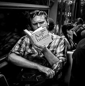 "Man reads book titles ""Assholes"" NYC subway - Black and white photography"