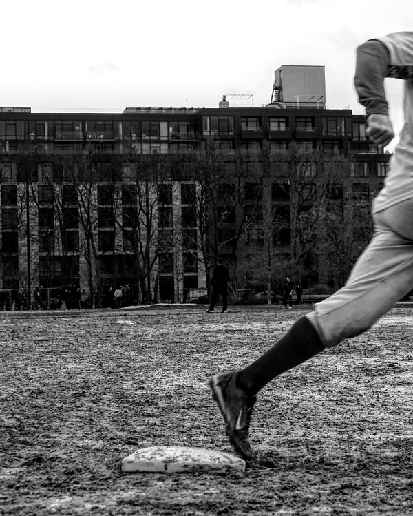 Man running on sports field - NYC - street photography - Black afnd white photography