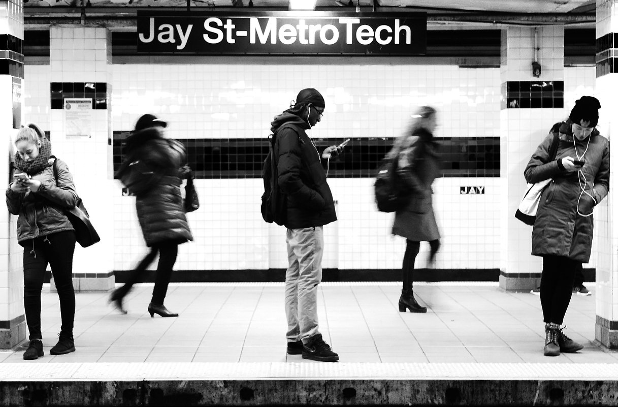 People on NYC subway platform at Jay street - Metro tech - Staring at cell phones - Black and white street photography