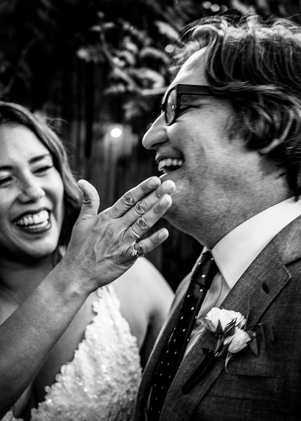 Bride wiping lipstick off grooms face at wedding - Black and white photography - Wedding photography