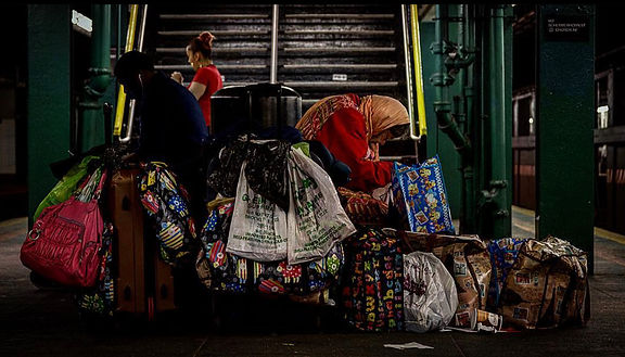 Homeless woman beside trash bags and her belongings on subway platform in NYC - Street photography