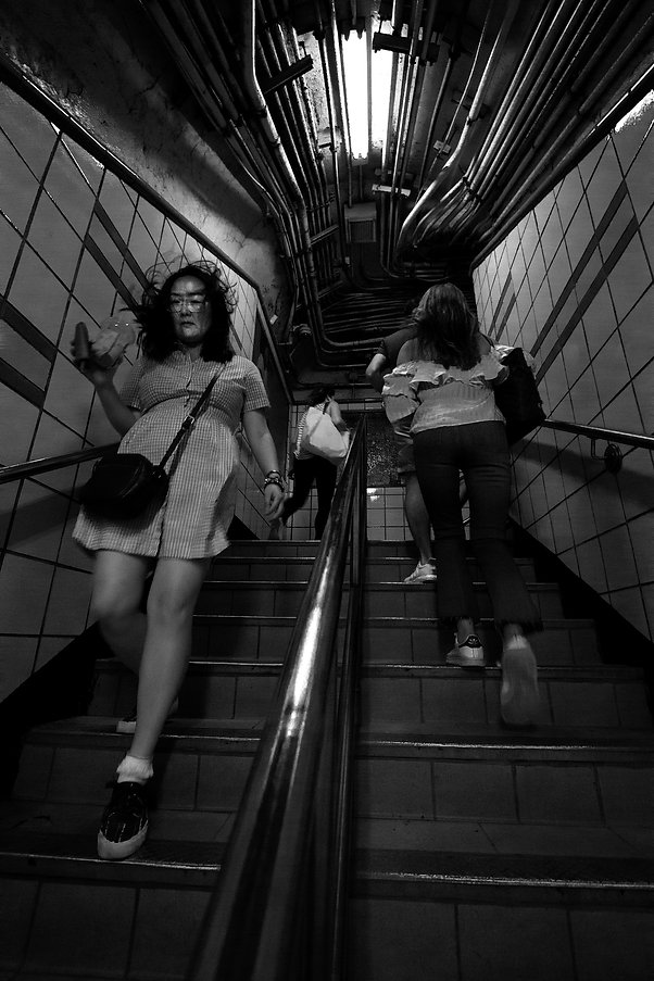 People running up and down stairs in NYC subway - Black and white street photography
