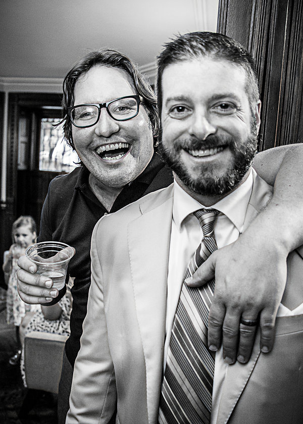 Male wedding guest with groom laughing at party  - Wedding photography - Black and white photography