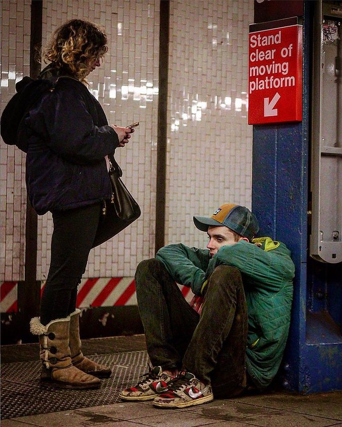Couple on a subway platform in NYC - Man sits on ground thinking - Street photography
